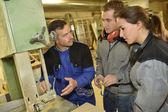 Teacher showing carpentry machinery — Stock Photo
