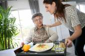 Home carer preparing lunch for woman — Photo