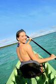 Woman paddling in canoe — Stock Photo