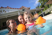 Family playing in swimming pool — Foto de Stock