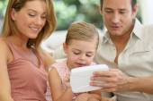 Parents with girl playing with tablet — Stock Photo