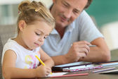 Daddy watching girl drawing — Stock Photo