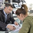 Car dealer editing purchase agreement — Stock Photo #67894127