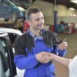 Mechanic giving car keys to customer — Stock Photo #67894525