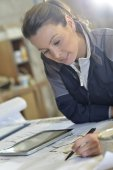 Female architect working with blueprint — Stockfoto