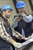 Engineer with worker checking on production — Stock Photo