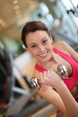Woman lifting dumbbells in gym — 图库照片