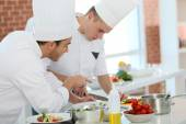 Chef training student in kitchen — Stock Photo