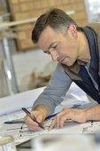 Architect designing on drafting table — Stock Photo