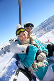 Couple on ski resort chairlift — Stock Photo