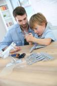 Father and son assembling airplane mock-up — Stock Photo