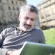 Man connected on tablet in park — Stock Photo #70975259
