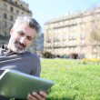 Man connected on tablet in park — Stock Photo #70976551