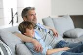 Father and son relaxing on sofa — Stock fotografie
