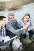 Biologist with students testing river water — Stock Photo