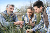 Teacher with students looking at vegetation — Stock Photo