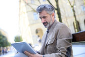 Man websurfing with tablet on bench — Stock Photo