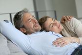 Mature couple relaxing on sofa — Stock Photo