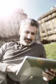 Man connected on tablet in park — Stock Photo