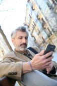 Guy using smartphone on bench — Zdjęcie stockowe