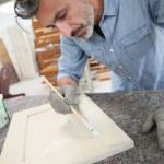 Carpenterin painting wood furniture — Stock Photo #72738227