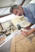 Carpenter working on wood furniture — Stock Photo