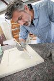 Carpenterin painting wood furniture — Stock Photo