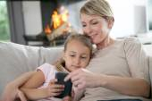 Mother and daughter playing with smartphone — Stock Photo