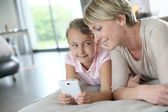 Mother and girl playing with smartphone — Stock Photo