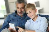 Daddy with son playing with smartphone — Stock Photo
