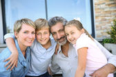Family in front of contemporary house — Stock Photo