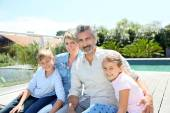 Family sitting by swimming-pool — Stock Photo
