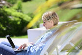 Woman using laptop on long chair — Stock Photo