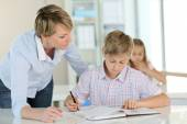 Teacher with schoolboy in classroom — Stock Photo