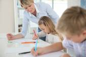 Teacher helping kids — Stock Photo