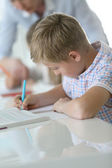 Schoolboy writing on notebook — Stock Photo