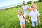 Family running in countryside — Stock Photo