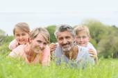 Family laying down on grass — Stock Photo