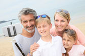 Family making picture with smartphone monopod — Stock Photo