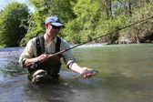 Fisherman catching brown trout — Stock Photo