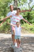 Family sitting on a trunk — Stock Photo
