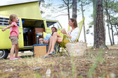 Family relaxing by camper van — Stock Photo
