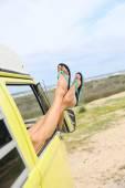Woman's feet on camper van window — Stock Photo