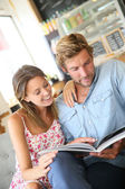 Trendy couple reading magazine — Stock Photo