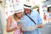 Couple in vacation looking at tourist guide — Stock Photo