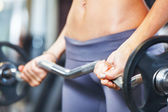 Young woman exercising with barbell in gym. — Stock Photo