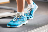 Woman running on treadmill in gym. — Stock Photo