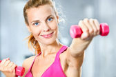 Young woman with dumbbells in her hands. — Stock Photo