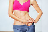 Closeup of young slim woman with six-pack torso. — Stock Photo