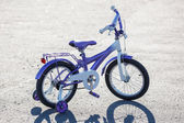 Small kids bike with training wheels outdoors. — Stock Photo